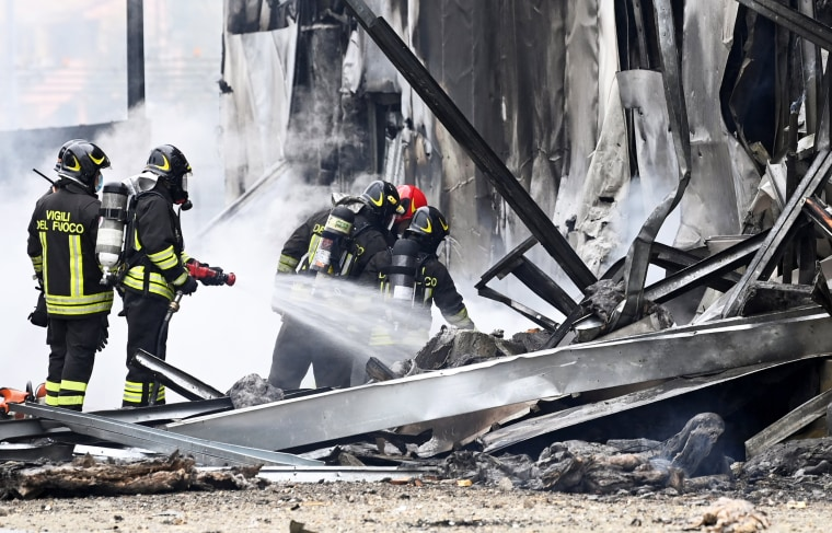 Firefighters work at the scene where a small plane crashed into a building in San Donato Milanese, Italy, on Oct. 3, 2021.