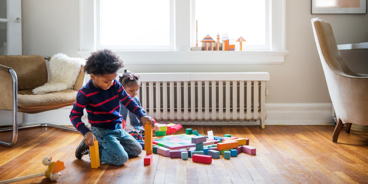 Brother and sister playing on floor at home with blocks