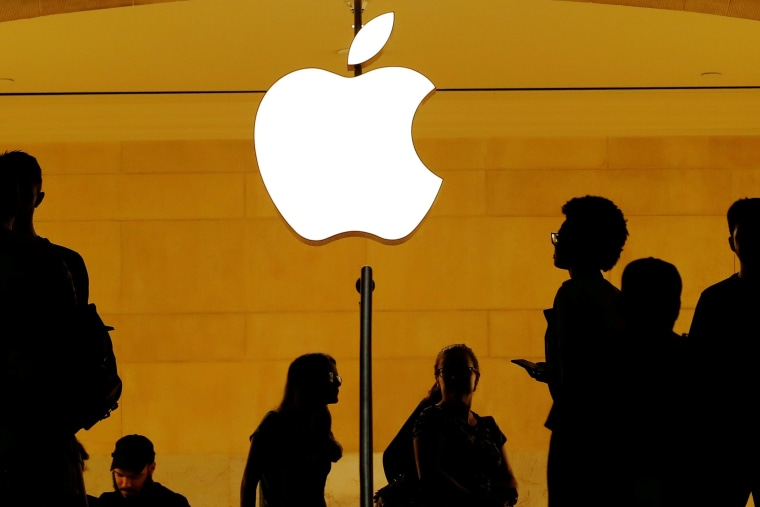 Image: FILE PHOTO: Customers walk past an Apple logo inside of an Apple store at Grand Central Station in New York