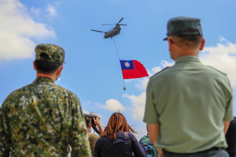 Taiwanese soldiers stand guard as a Chinook Helicopter carrying a tremendous Taiwan flag flies over a military camp as part of a rehearsal for Taiwan's Double-Ten National Day Celebration on Sept. 28, 2021.
