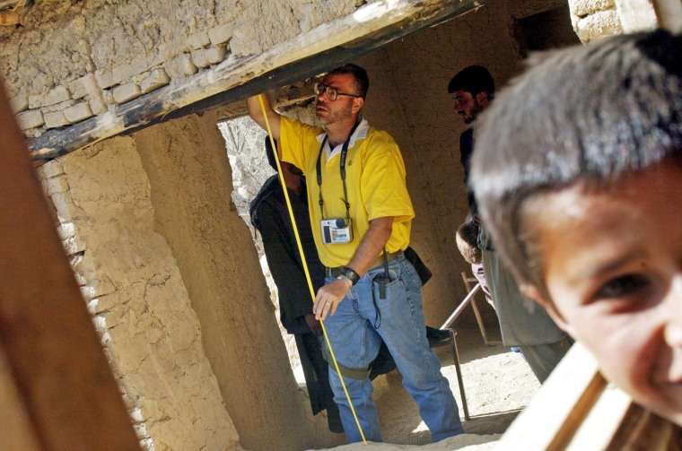 A Civil Affairs Battalion major measures an opening for a window in a school on April 2, 2002, near the Bagram Air Base in Afghanistan.