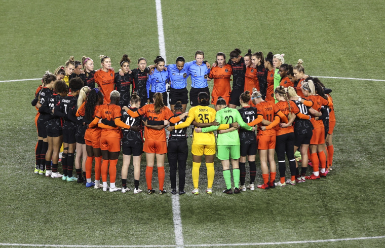 Image: Portland Thorns and Houston Dash players, along with referees, gather at midfield, in demonstration of solidarity with two former NWSL players