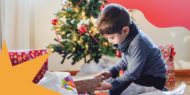 Little boy opening Christmas present under Christmas tree