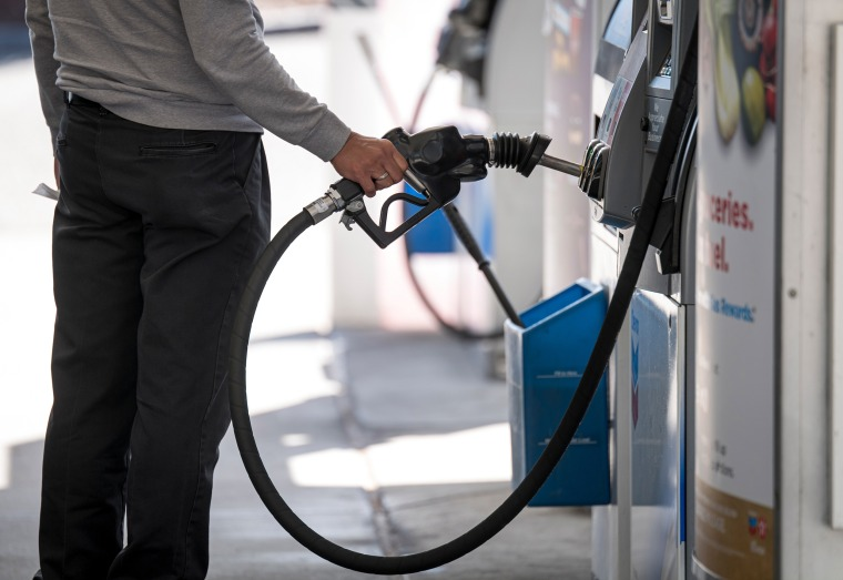 Image: A person holds a fuel pump nozzle at a Chevron Corp. gas station in Colma, Calif.