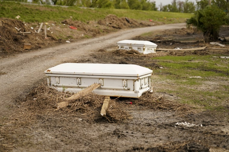 Caskets that floated from their tombs during flooding from Hurricane Ida sit along a roadside in Ironton, La., on Sept. 27, 2021.