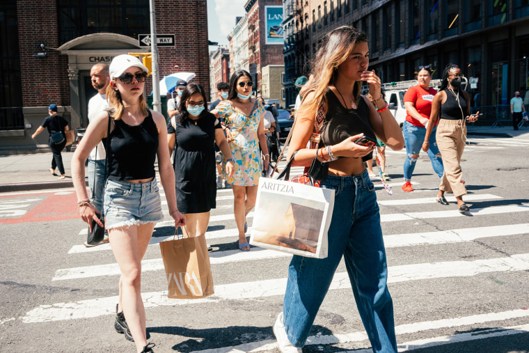 Image: Pedestrians carrying shopping bags cross a street in New York on Aug. 25, 2021.