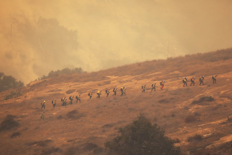 Image: Firefighters from California Conservation Corps prepare as flames from the Alisal Fire move toward La Paloma Ranch near Refugio Canyon on Oct. 12, 2021.