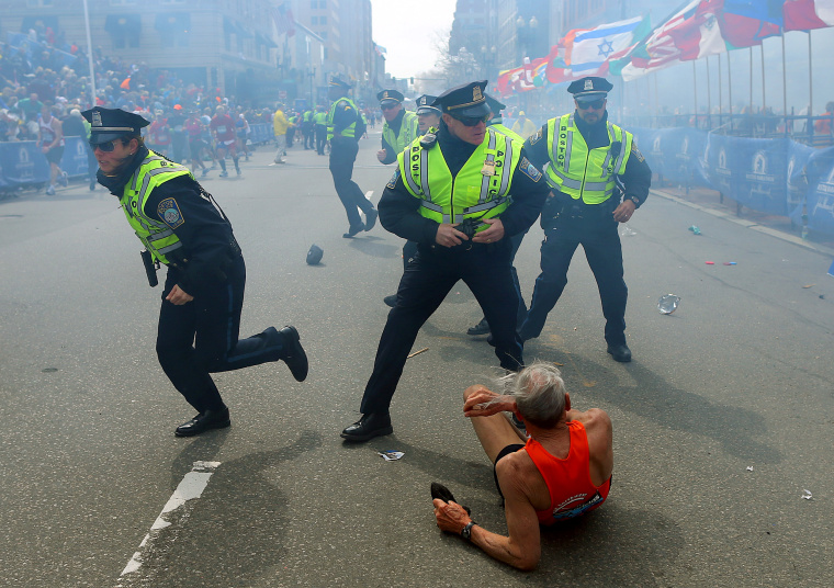 Image: Police officers draw their guns as a second explosion occurs during the Boston Marathon on April 15, 2013.