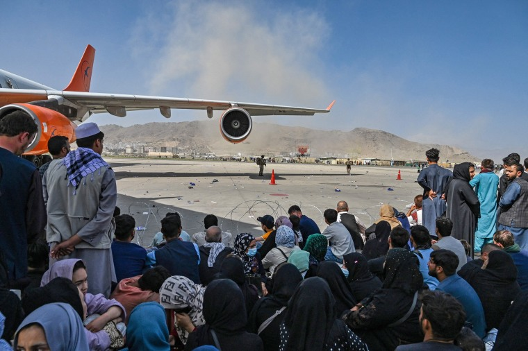 Afghan wait to leave the airport in Kabul on Aug. 16, 2021.