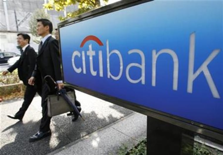 Men walk past a Citibank sign outside its Tokyo branch last month. Moody's Investors Service cut its ratings on Citigroup Inc debt by a notch, the latest embarrassment for the largest U.S. bank, and putting it under renewed pressure to shore up its shrinking capital base.