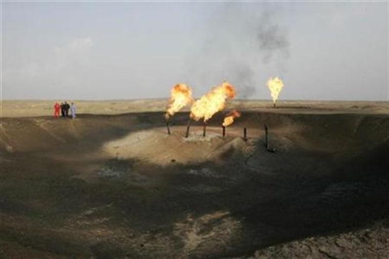 Workers walk near flames of burning excess gas at Fakka oilfield, near Amara