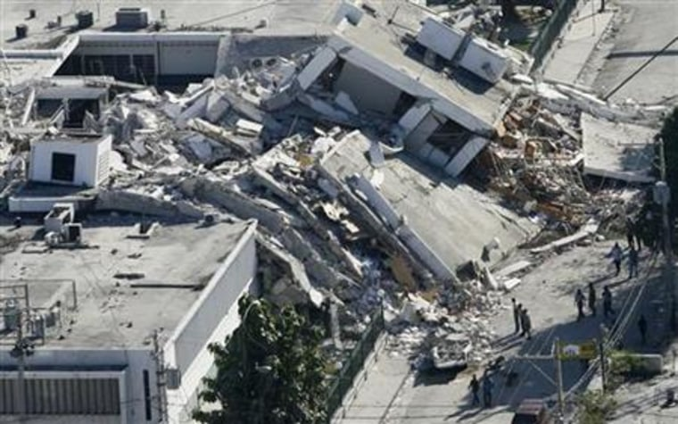 Haitians survey the damage to a building that collapsed onto a road in downtown Port-au-Prince