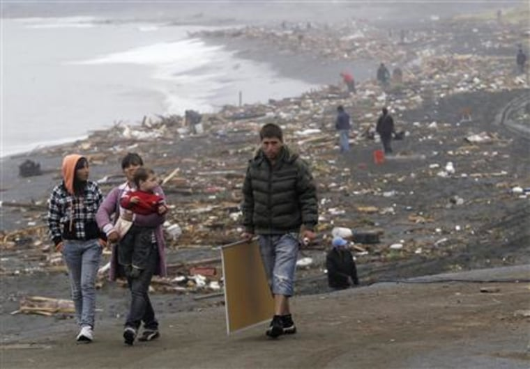 Residents recover items from the debris left by waves generated by a major earthquake, near the epicenter in Pelluhue