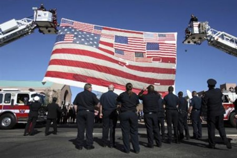 Firefighters raise an American flag recovered from Ground Zero after the September 11 attacks in New York City at St. Elizabeth Ann Seton Church at the funeral of 9-year-old Christina Green in Tucson, Arizona