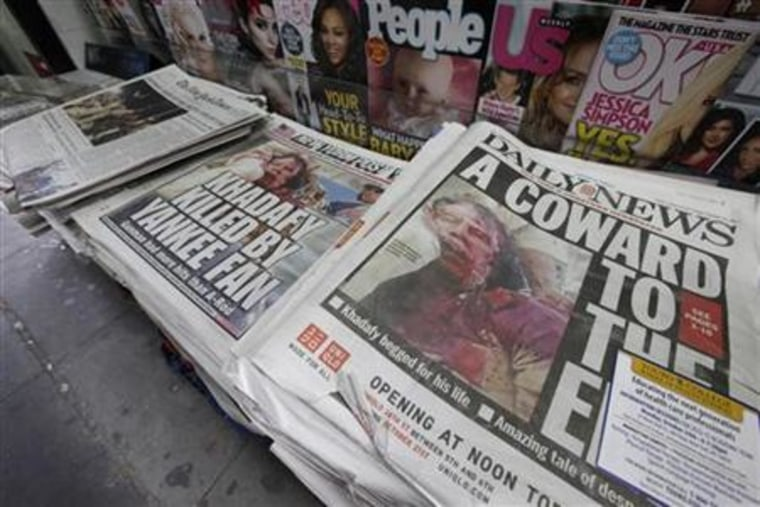 Newspapers featuring the death of former Libyan leader Muammar Gaddafi are seen at a news stand in New York