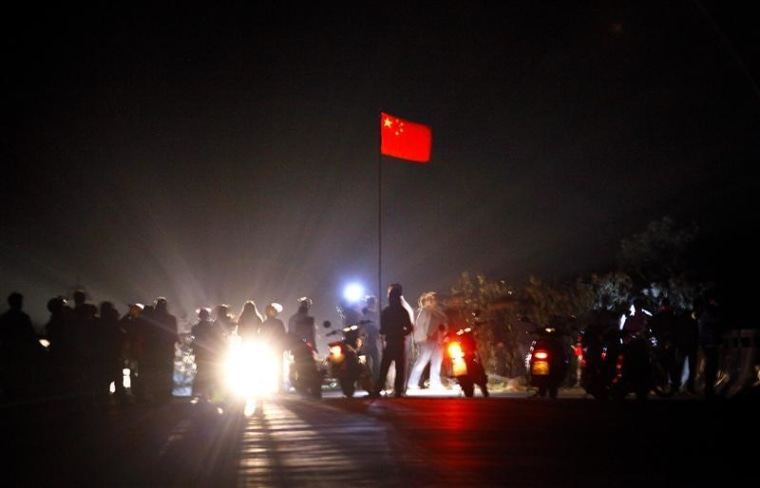 The Chinese national flag flies from a make-shift mast as residents of the village of Wukan in Lufeng county, Guangdong province remove a barricade