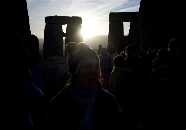 Revellers watch as the sun rises at Stonehenge on Salisbury plain in southern England