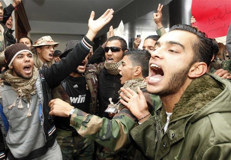 Former fighters protest at the office of Libya's Prime Minister Abdurrahim El-Keib in Tripoli