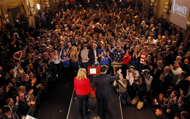 Republican presidential candidate and former Massachusetts Governor Mitt Romney holds hands with his wife Ann as he addresses supporters at his Iowa Caucus night rally in Des Moines