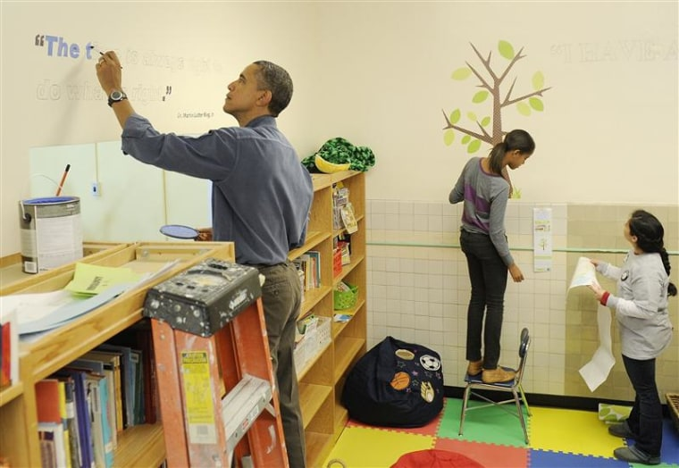 Obama paints a quotation attributed to slain civil rights leader Martin Luther King Jr while he and his daughter work during a day of service in King's honor at the Browne Education Campus school in Washington