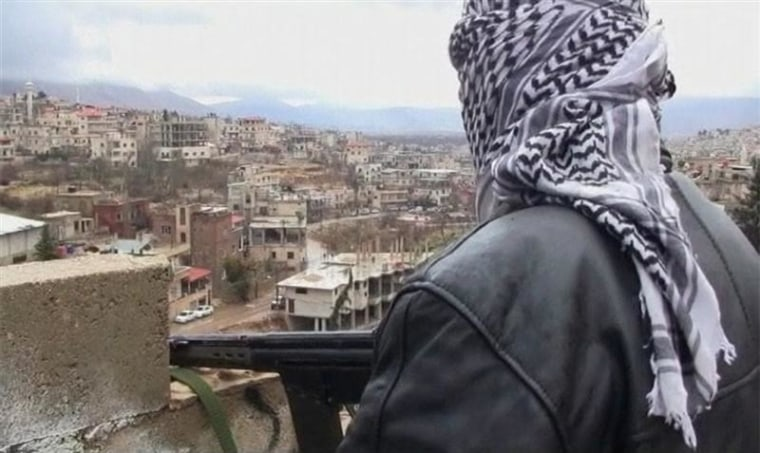 A member of the Free Syrian Army with an assault rifle stands guard during a patrol in the western border town of Zabadani