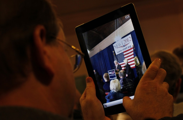 File photo of a man taking pictures of Republican presidential candidate Gingrich with an Apple iPad during a campaign stop in Plymouth, New Hampshire