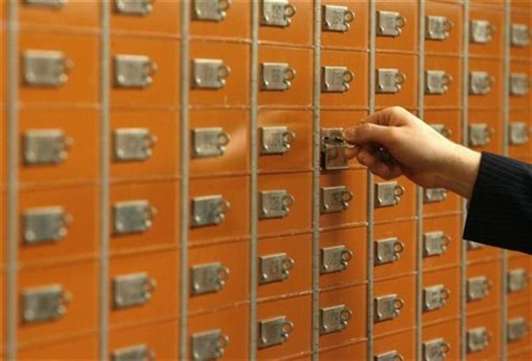 An employee checks a safe box in the vault of the Basler Kantonalbank (BKB) in Basel