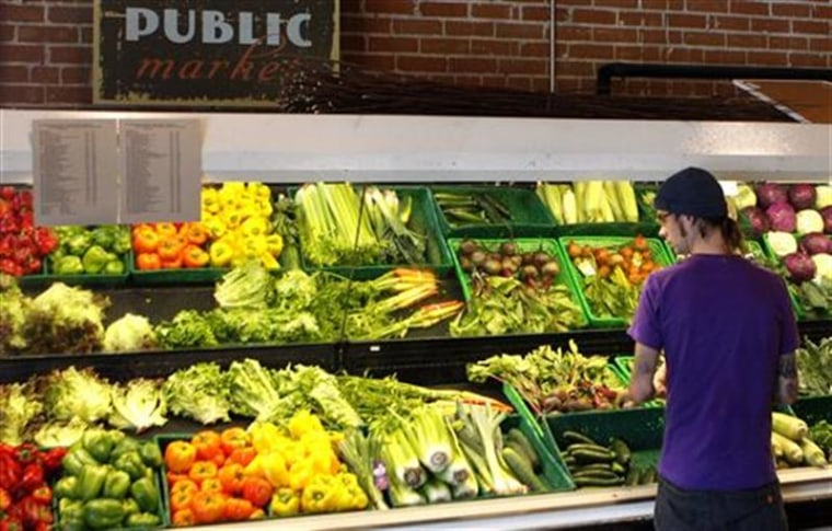 A customer looks over produce at the Phoenix Public Market in Phoenix