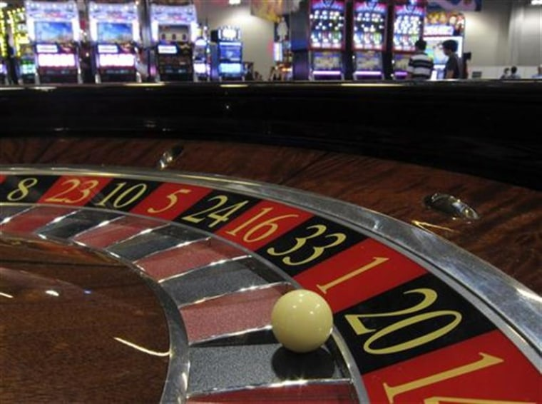 Ball is seen on a roulette wheel in front of slot machines at Gaming Expo Asia in Macau
