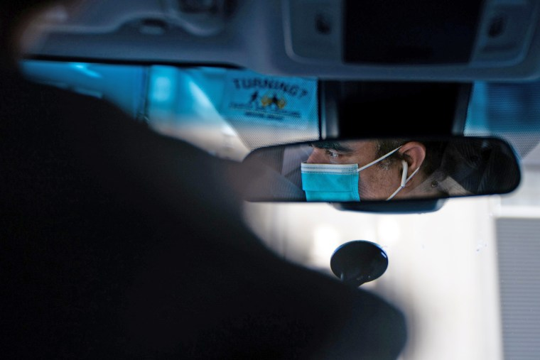 Image: An Uber driver in a surgical mask is seen in a mirror in the Manhattan borough following the outbreak of the coronavirus disease