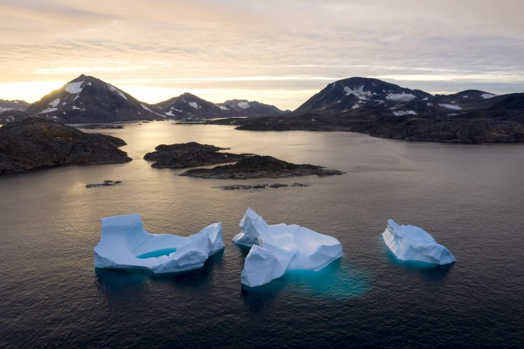 Large Icebergs float away as the sun rises near Kulusuk, Greenland on Aug. 16, 2019.