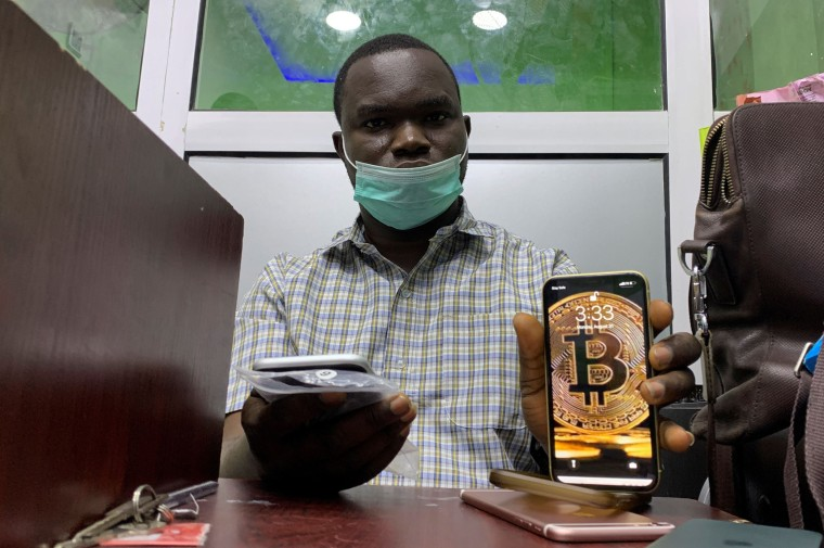 """Image: Abolaji Odunjo, a gadget vendor who trades with bitcoin, poses with his mobile phone after an interview with Reuters at his store at the '""""Computer village"""", in Lagos"""