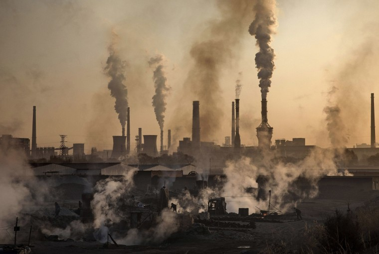 Image: Smoke billows from a large steel plant as a Chinese laborer works at an unauthorized steel factory in Inner Mongolia, China.