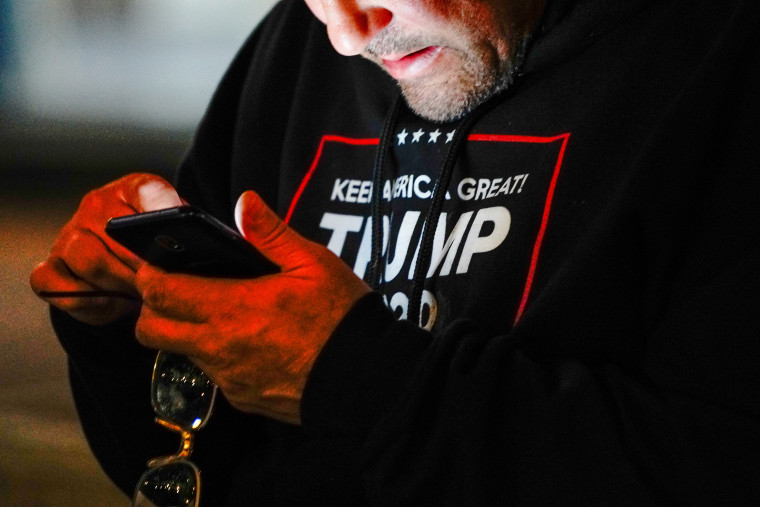 """A man wearing a """"Trump 2020"""" sweatshirt uses his mobile phone during a """"Stop the Steal"""" protest outside Milwaukee Central Count the day after Milwaukee County finished counting absentee ballots, in Milwaukee"""