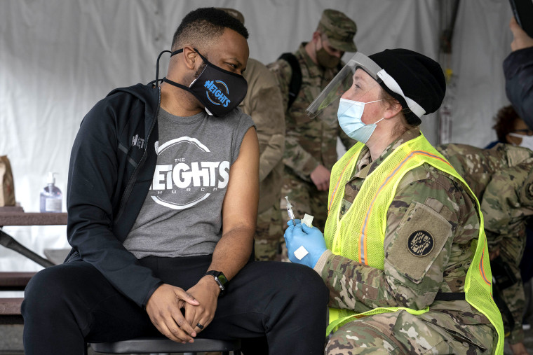 Image: A man speaks with a member of the National Guard after receiving a coronavirus vaccine in the parking lot of Six Flags on Feb. 6, 2021 in Bowie, Md.
