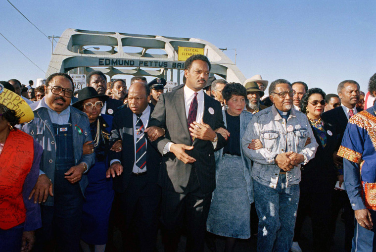 Civil rights figures lead marchers across the Edmund Pettus Bridge during the recreation of the 1965 Selma to Montgomery march in Selma, Ala., March 4, 1990.