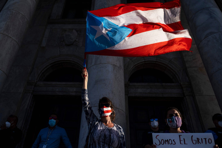 An activist holds a Puerto Rican flag in front of the Capitol during a demonstration to mark International Women's Day in San Juan on March 8, 2020.