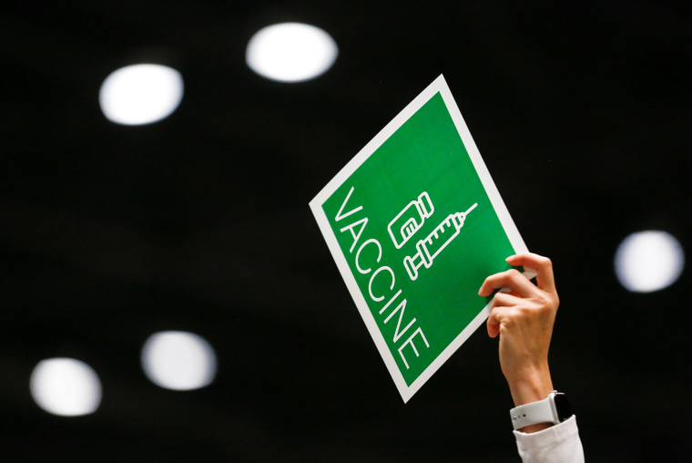 A worker holds up a sign to signal their station needs more vaccine doses as people attend a coronavirus disease vaccination site at Lumen Field Event Center in Seattle, on March 13, 2021.