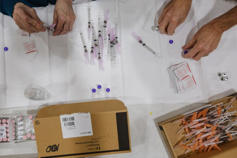 Image: Healthcare workers prepare doses of the Pfizer-BioNTech Covid-19 vaccine to administer to staff members of the Clarendon School District at Manning High School in Manning, S.C.,