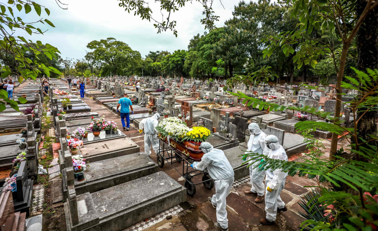 Image: Cemetery workers carry a coffin during the burial of a person who died from Covid-19 at the Sao Joao municipal cemetery in Porto Alegre, Brazil, on March 26, 2021.