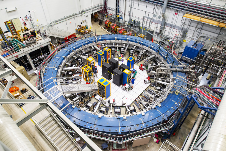The Muon g-2 ring sits in its detector hall amidst electronics racks, the muon beamline, and other equipment. This impressive experiment operates at negative 450 degrees Fahrenheit and studies the precession, or wobble, of muons as they travel through the magnetic field.