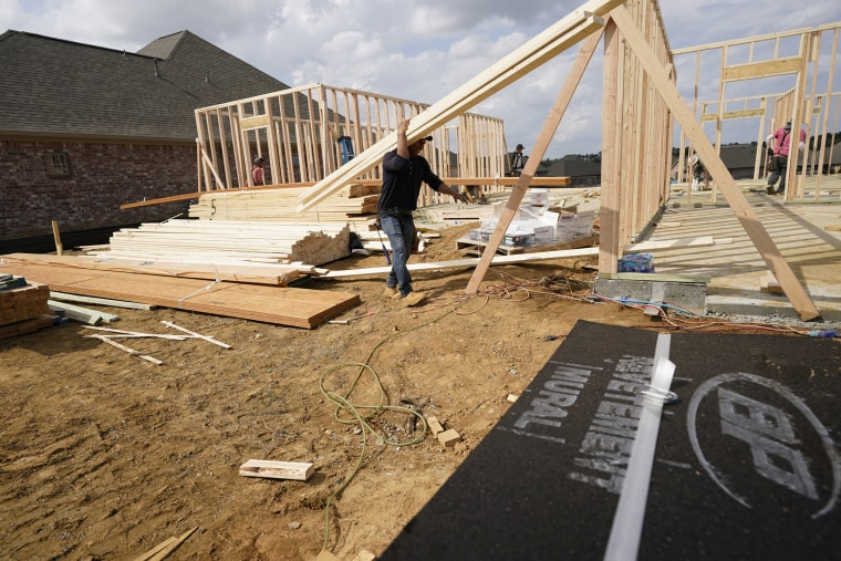 A workman carries beams at a new housing site in Madison County, Miss., on March 16, 2021.
