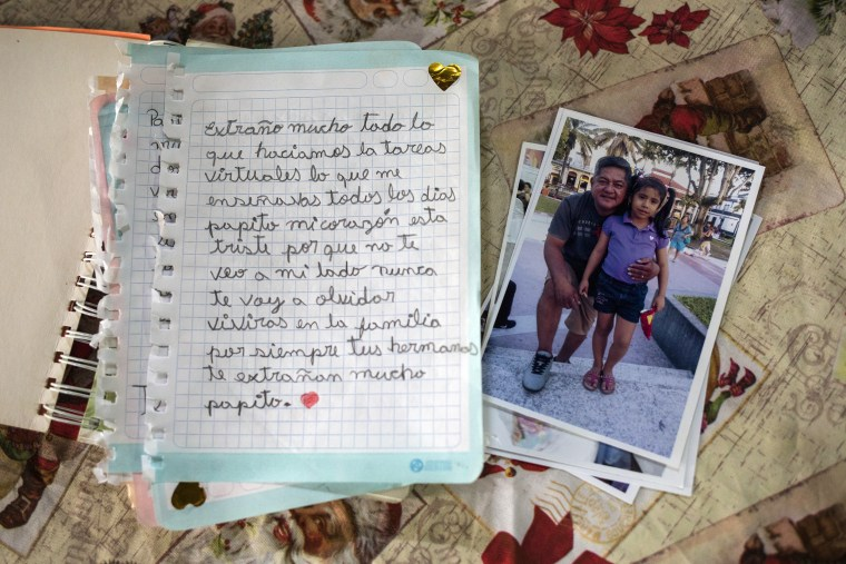 Image: A letter written by 9-year-old Adriana Wong to her late father Herman Wong who died of Covid-19, sits next to a photo showing Adriana when she was 5-years-old with her father, in Iquitos, Peru, on March 21, 2021