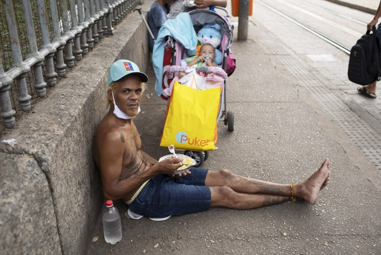 A man eats a meal donated by the Leao Xlll Foundation amid the Covid-19 pandemic in Rio de Janeiro, Wed April 7, 2021.