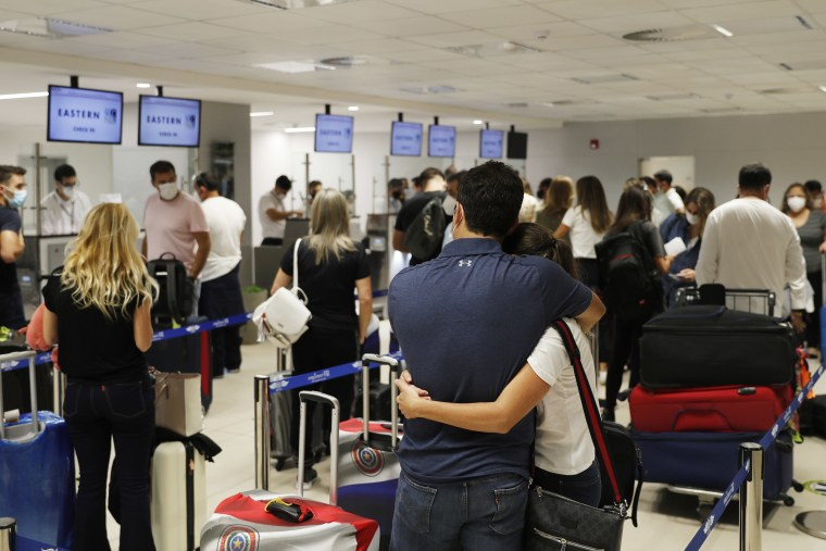 Passengers check in for a flight to Miami at Silvio Pettirossi Airport, in Luque, Paraguay on April 17, 2021.