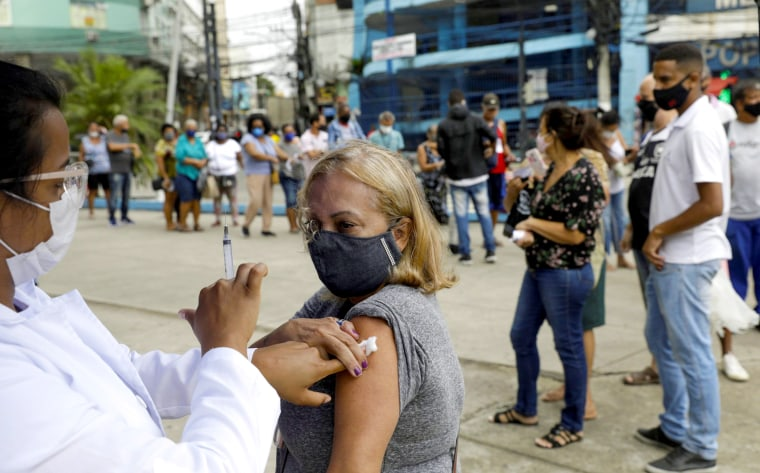 Image: A health worker shows the syringe to a citizen after applying a dose of the AstraZeneca Covid-19 vaccine, during a vaccination day for 57-year-old and older citizens, in Duque de Caxias near Rio de Janeiro, Brazil on April 21, 2021.