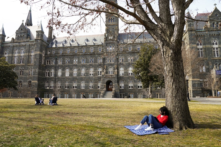 A student studies in the sunshine at Georgetown University in Washington on March 9, 2021.