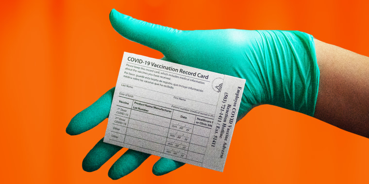 A gloved hand holds a CDC Covid-19 vaccination record card.