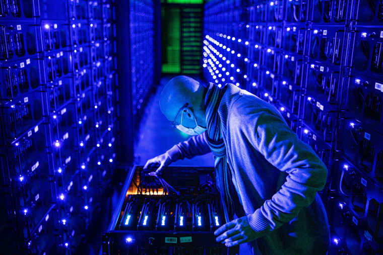 An employee inspects graphics processing units at the Evobits crypto farm in Cluj-Napoca, Romania, on Jan. 22, 2021.