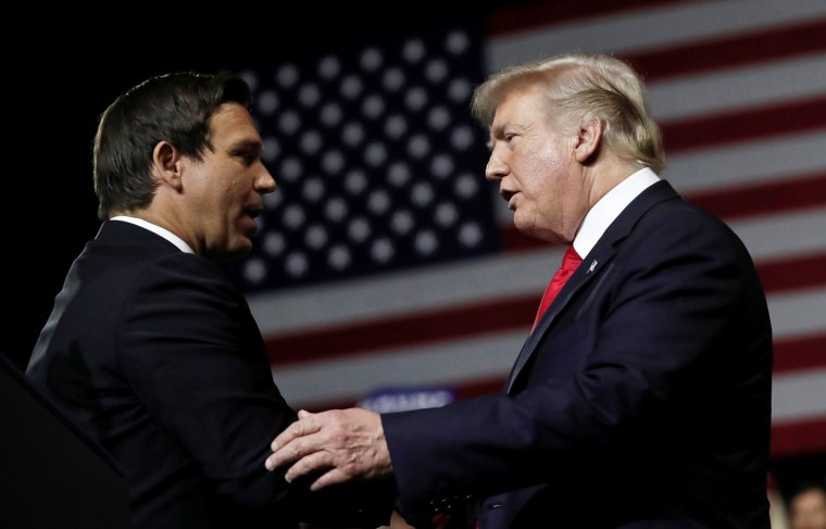 President Donald Trump talks with Republican Florida governor candidate Ron DeSantis during a Make America Great Again Rally at the Florida State Fairgrounds in Tampa, Florida, on July 31, 2018.
